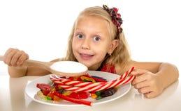 Criança fêmea caucasiano consideravelmente feliz que come o prato completamente dos doces na dieta perigosa do abuso doce do açúc imagens de stock