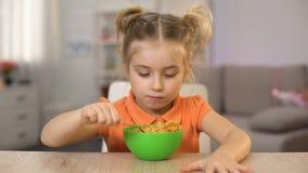 Criança fêmea com fome que come flocos de milho com leite e que mostra os polegares acima, café da manhã filme