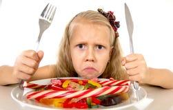 Criança fêmea consideravelmente caucasiano que come o prato completamente dos doces na dieta perigosa do abuso doce do açúcar imagem de stock