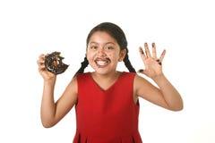 Criança fêmea latino-americano no vestido vermelho que come a filhós do chocolate com mãos e a boca manchada e sorriso sujo feliz Fotografia de Stock Royalty Free
