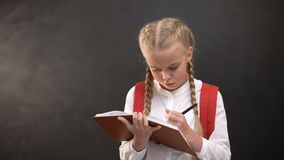 Criança fêmea pensativa com a mochila que faz trabalhos de casa, tendo uma ideia, educação vídeos de arquivo