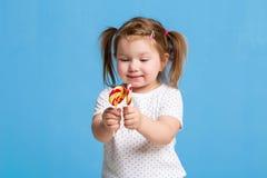 Criança fêmea pequena bonita que mantém feliz de sorriso dos doces enormes da espiral do pirulito isolado no fundo azul Fotos de Stock Royalty Free