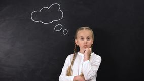 Criança fêmea que pensa sobre o ensino universitário futuro, sinal da ideia no quadro-negro vídeos de arquivo