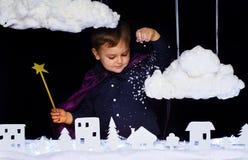 A criança fabulosa joga a neve sobre a cidade no Natal Imagem de Stock Royalty Free