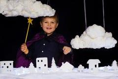 A criança fabulosa joga a neve sobre a cidade no Natal Fotografia de Stock Royalty Free