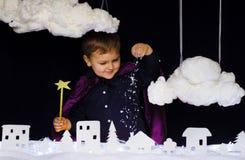 A criança fabulosa joga a neve sobre a cidade no Natal Imagem de Stock