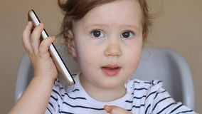 A criança fala pelo telefone vídeos de arquivo