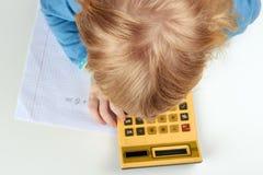 A criança faz cálculos com calculadora retro Imagens de Stock Royalty Free