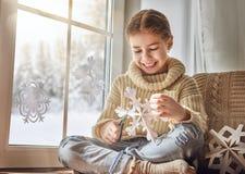 A criança faz os flocos de neve de papel fotografia de stock