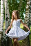 A criança feliz é de dança e de jogo no vestido branco foto de stock