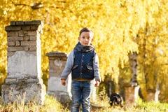 A criança feliz anda no parque Autumn Day brilhante Árvores com folha amarela outubro morno foto de stock