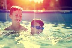 A criança feliz aprende a natação com estilo do vintage do irmão Fotos de Stock