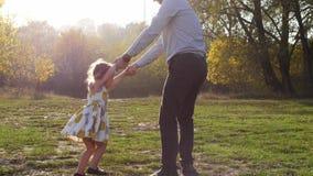 A criança feliz apressa-se nas mãos do pai Pai que gira sua filha filme