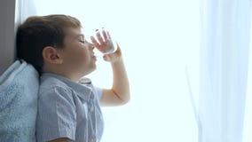 A criança feliz bebe a água do vidro que senta-se na janela em casa vídeos de arquivo