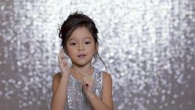 Criança feliz bonito da menina em uma dança de prata do vestido no fundo do bokeh de prata vídeos de arquivo