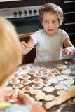 Criança feliz com a mãe que faz bolinhas de massa Fotos de Stock Royalty Free