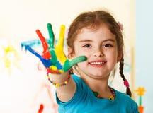 Criança feliz com mãos pintadas Imagem de Stock