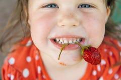 Criança feliz com morangos Fotografia de Stock Royalty Free