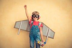 Criança feliz com o jetpack do brinquedo que joga em casa Imagens de Stock
