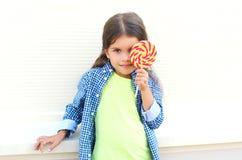 Criança feliz com o pirulito doce do caramelo que tem o divertimento Fotografia de Stock