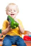 Criança feliz com pimenta verde Fotografia de Stock