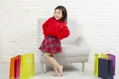 Criança feliz com sacos de compras Sorriso da menina de compra A bonito imagem de stock royalty free