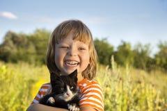 Criança feliz com um gatinho Foto de Stock Royalty Free