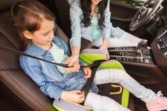Criança feliz da asseguração da mulher com o cinto de segurança no carro imagens de stock