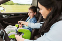 Criança feliz da asseguração da mulher com o cinto de segurança no carro imagem de stock