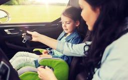 Criança feliz da asseguração da mulher com o cinto de segurança no carro imagens de stock royalty free