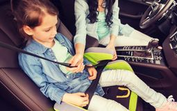 Criança feliz da asseguração da mulher com o cinto de segurança no carro foto de stock royalty free