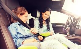 Criança feliz da asseguração da mulher com o cinto de segurança no carro foto de stock