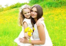 A criança feliz da mãe e da filha junto com o dente-de-leão amarelo floresce Fotografia de Stock Royalty Free