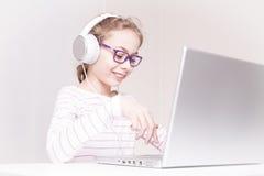 Criança feliz da menina da criança nos fones de ouvido usando o laptop foto de stock