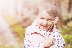 Criança feliz de fala do telefone da menina bonito feliz da criança pequena fora fotografia de stock royalty free