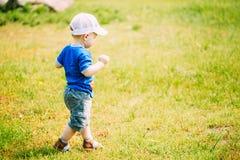 Criança feliz de Little Boy que corre no verde do verão Imagens de Stock Royalty Free
