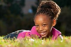 Criança feliz do americano africano que encontra-se em uma grama Fotografia de Stock Royalty Free