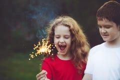 Criança feliz do amigo no partido com o chuveirinho ardente em sua mão imagens de stock