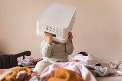 Criança feliz do bebê do divertimento com a cesta de lavanderia na cabeça e pilhas em torno dele fotografia de stock