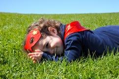 Criança feliz do super-herói colocada na grama verde foto de stock royalty free