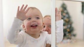 Criança feliz e mãe que olham o Natal da janela vídeos de arquivo