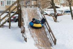 A criança feliz está dirigindo para congelar a montanha para a tubulação no inverno Fotografia de Stock Royalty Free