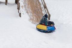 A criança feliz está dirigindo para congelar a montanha para a tubulação no inverno Imagens de Stock