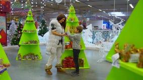 A criança feliz está vindo a sua mãe e está mostrando alegremente a bola da neve Lugar da alameda durante feriados do Natal vídeos de arquivo