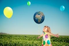 Criança feliz fora no campo da mola Foto de Stock