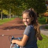 A criança feliz monta uma bicicleta em um trajeto da bicicleta foto de stock