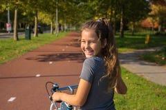 A criança feliz monta uma bicicleta no trajeto da bicicleta imagem de stock