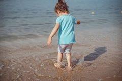 Criança feliz na areia na praia tropical fotografia de stock royalty free
