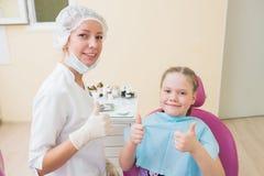 Criança feliz na cadeira do dentista com o doutor fêmea que mostra os polegares acima na clínica dental foto de stock