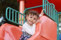 Criança feliz no campo de jogos do parque fotografia de stock